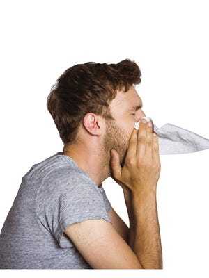 Close up side view of man blowing nose