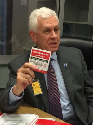 "Bill Gibbons, president of the Crime Commission and the University of Memphis' Public Safety Institute, holds up a card for ""The Crime Plan: 2017-2021,"" for Memphis and Shelby County. The plan, devised by Operation: Safe Community, includes an approach which assigns community prosecutors to selected areas."