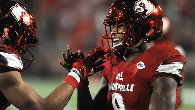 Louisville quarterback Lamar Jackson (8) celebrates with Reggie Bonnafon after Bonnafon scores a touchdown against Syracuse on Saturday at Papa John's Cardinal Stadium. Nov. 18, 2017