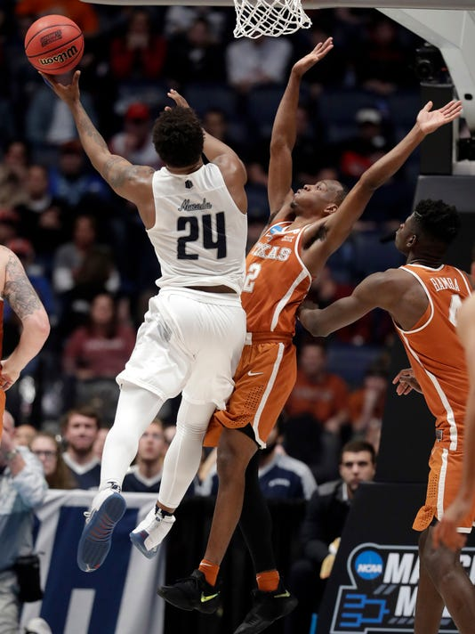 Nevada guard Jordan Caroline (24) drives to the basket against Texas guard Matt Coleman (2) in the second half of a first-round game of the NCAA college basketball tournament in Nashville, Tenn., Friday, March 16, 2018. (AP Photo/Mark Humphrey)