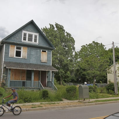 Grass grows out of control at the foreclosed house at 206 N. Union St. and detracts from the city neighborhood.   SHAWN DOWD/@sdowdphoto/STAFF PHOTOGRAPHER A boarded up and foreclosed house at 206 N. Union Street in Rochester Wednesday, June 4, 2014.  The vacant building, with grass up to waist-high, is one of dozens of zombie properties in the city.