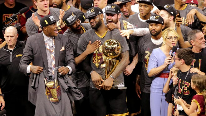 Cleveland Cavaliers forward LeBron James (23) celebrates with the Larry O'Brien Championship Trophy after beating the Golden State Warriors in game seven of the NBA Finals at Oracle Arena.