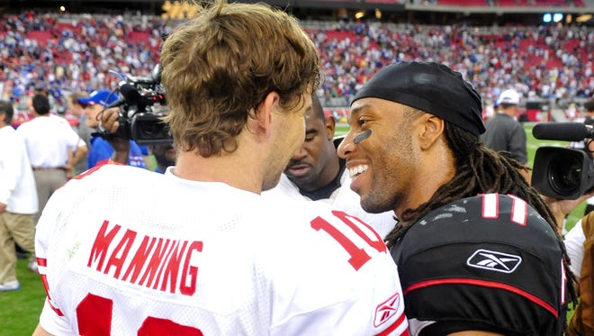 New York Giants quarterback Eli Manning (10) and Arizona Cardinals wide receiver Larry Fitzgerald (11) talk after a 31-27 victory by the Giants at University of Phoenix Stadium in 2011.