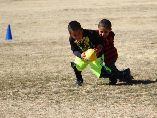 Children playing football at the Hornet's Super Bowl Saturday Family Event.