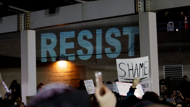 The protesters' sentiments are projected onto a wall of the JFK International Airport on Jan. 28, 2017.