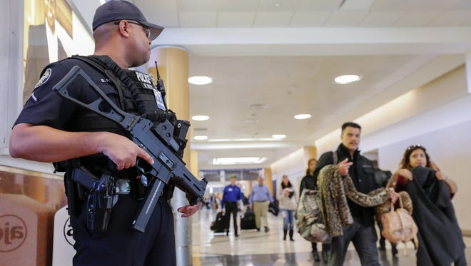 A heavily armed officer with the Atlanta Police Department stands guard in the main domestic terminal at Hartsfield-Jackson Atlanta International Airport in Atlanta, Ga., on Nov. 16, 2015.