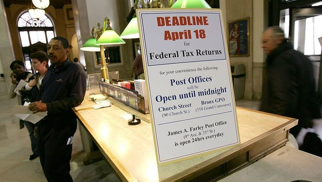 People walk past a sign declaring tax deadline day.