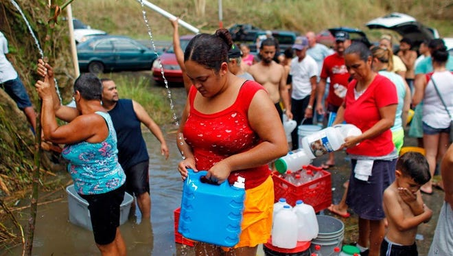 People collect water from a natural spring created by landslides in a mountain next to a road in Corozal, Puerto Rico, on Sept. 24, 2017.
