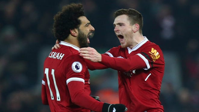 Liverpool's Andrew Robertson celebrates with Mohamed Salah after Salah scored his side's fourth goal against Manchester City.