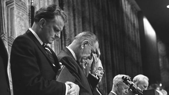 President Lyndon B. Johnson bows his head at the 14th