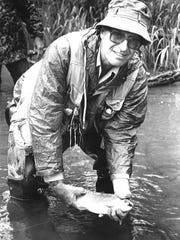 An avid fisherman, David Rossie shows off his catch in 1990.