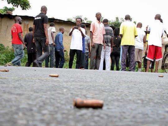 A man looks across at spent bullet casings lying on