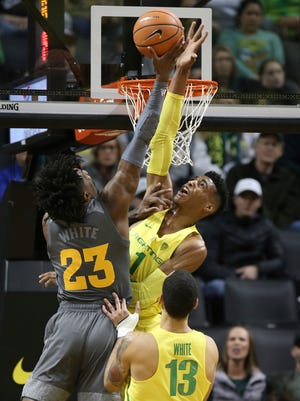 Arizona State's Romello White, left, has his shot blocked by Oregon's Kenny Wooten, with Oregon's Paul White, foreground right, watching during the first half of an NCAA college basketball game Thursday, Feb. 22, 2018, in Eugene, Ore.