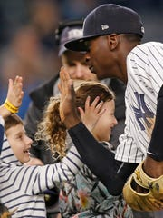 New York Yankees shortstop Didi Gregorius (18) trades high fives with youngsters participating in the Yankees HOPE (Helping Others Persevere and Excel) Week after a baseball game at Yankee Stadium in New York, Wednesday, May 24, 2017. Gregorius hit a solo home run in the Yankees 3-0 shutout of the Kansas City Royals.
