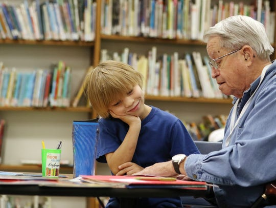 Volunteer Charlie Rembert reads with then second-grader