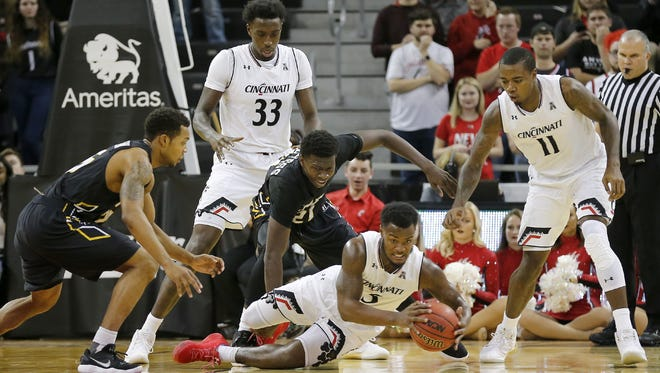 University of Cincinnati guard Trevor Moore (5) collects a loose ball against Arkansas-Pine Bluff on Tuesday. The Bearcats won 77-49.