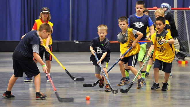 Everyone goes for the puck during a game of street hockey at the Music City Sports Festival on Saturday at Music City Center.