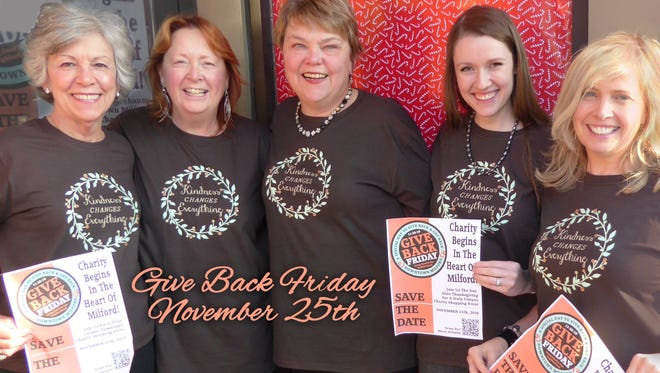 Staff members from The Clothing Cove wear T-shirts they'll sell on Give Back Friday in Milford.