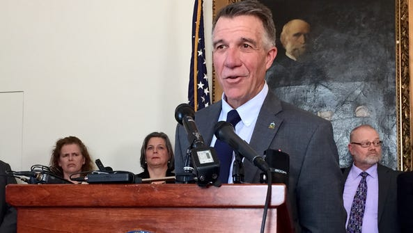 Gov. Phil Scott speaks to reporters at the Statehouse