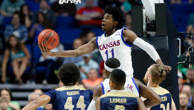 Kansas' Josh Jackson (11) goes up for a shot over UC Davis' Garrison Goode (44), Brynton Lemar (0) and Mikey Henn (24) in the first half of a first-round game in the men's NCAA college basketball tournament in Tulsa, Okla., Friday March 17, 2017.
