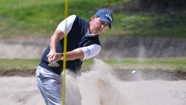 Phil Mickelson plays a shot from a bunker on the first