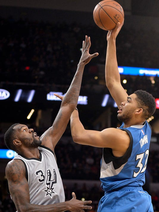 Minnesota Timberwolves center Karl-Anthony Towns, right, shoots against San Antonio Spurs center Dewayne Dedmon during the first half of an NBA basketball game, Saturday, March 4, 2017, in San Antonio. (AP Photo/Darren Abate)
