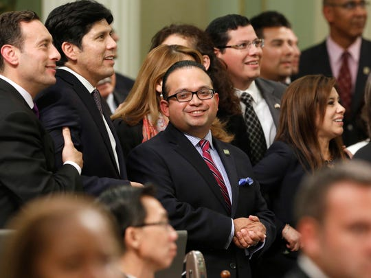 In this Sept. 12, 2013 photo, Assemblyman Luis Alejo, D-Watsonville, center, smiles as he and other members of the Latino Caucus watch the votes being posted for Alejo's immigrant driver's license bill that was approved by the Assembly in Sacramento, Calif. California has about two dozen Latino lawmakers, yet that's just half their proportion of the state' population. Minorities remain significantly underrepresented in most state Legislatures and Congress despite comprising a growing share of the U.S. population, according to an analysis of demographic data by the Associated Press.