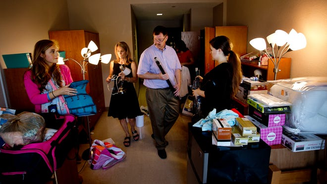 Caitlin Bostrom, left, and Marisa Helms, right, get help from parents, Collete Bostrom, center left, and Mark Helms, center right, as they move into the dorms at Ave Maria University..