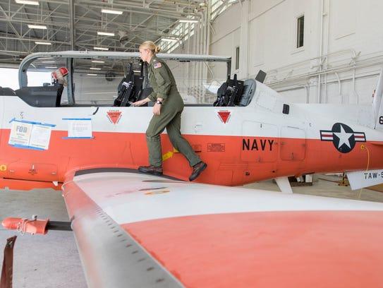 Lt. Ashley Hallford climbs into a T-6B Texan aircraft
