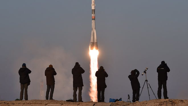 Photographers take pictures as Russia's Soyuz TMA-19M spacecraft takes off on Dec. 15 for the International Space Station.