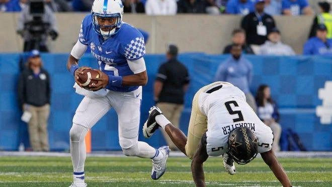 Kentucky Wildcats quarterback Stephen Johnson (15) runs the ball against Vanderbilt Commodores cornerback Torren McGaster (5) in the second half at Commonwealth Stadium. Kentucky defeated Vanderbilt 20-13.