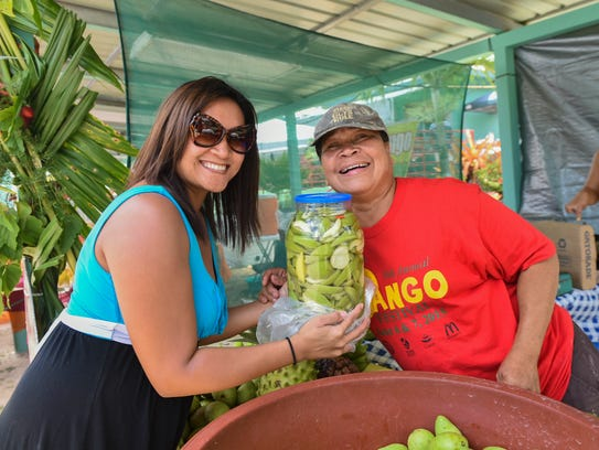 Jolynh Brubaker, left, purchases a jar of mangoes from