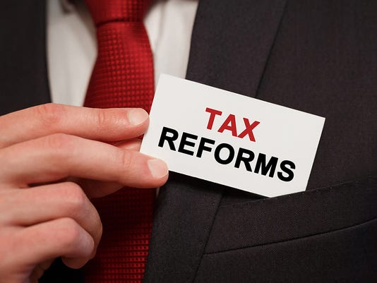Businessman putting a card with text Tax Reforms in the pocket