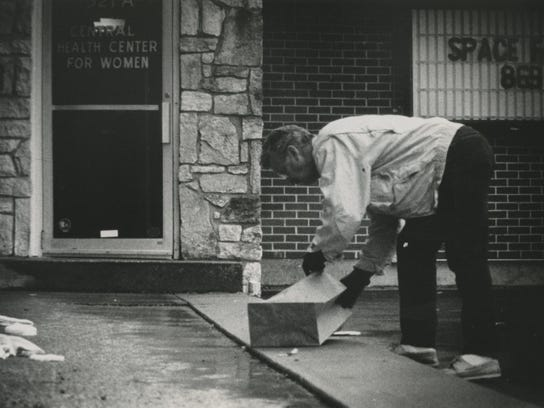 A man cleans up outside the clinic after the shooting.