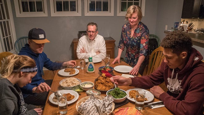 """It's dinner time at the Birchlers. From left are Kaelyn Denker, Gavin Hain (Kaelyn's boyfriend), John Birchler, Laurie Birchler and K'Andre Miller. They are about to feast on fried chicken with honey mustard sauce. """"It's one of the faves on the list,"""" Laurie says."""