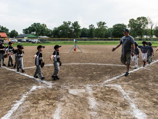 The St. Joe (left) and Scott (right) little league baseball teams line up to high-five one another at the end of the game held at the Scott Township baseball fields in Evansville, Indiana, June 5, 2017.
