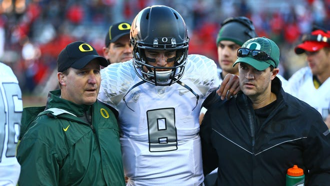 Oregon quarterback Marcus Mariota (center) is helped off the field after suffering a head injury on a tackle attempt in the fourth quarter Saturday against Arizona.