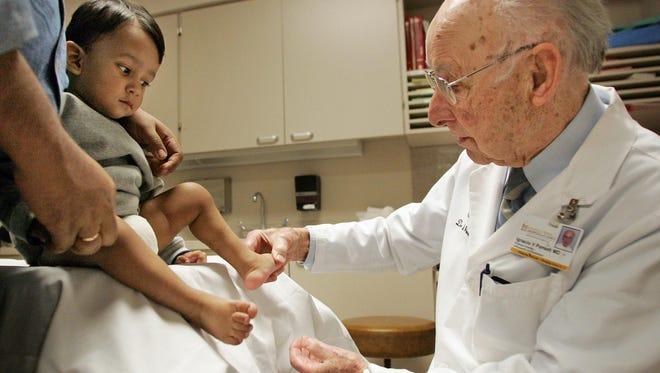 Dr. Ignacio Ponseti examines the feet of Adrij Roy at University Hospitals in Iowa City in 2007.
