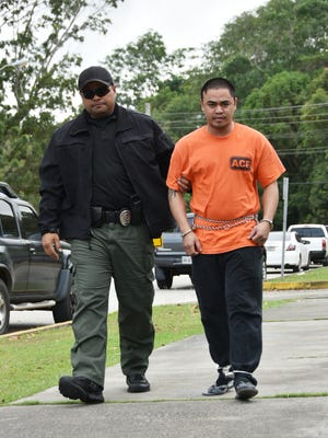 Domingo Sylvester Chargualaf Mendiola, right, is escorted by Criminal Justice Strike Force Officer J.J. Remoket to the Guam Police Department Hagatna precinct upon his arrest on Thursday, Jan. 21.