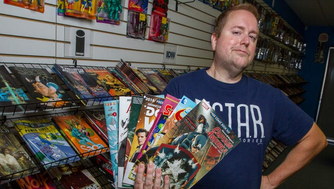 "Tom Lotz, owner of Cool Comics and Games in Cape Coral, displays a handful of samples that will be given away for free to customers Saturday (5/7/16) as part of ""Free Comic Book Day"". Local comic book stores will be handing out hundreds of free comic books to visiting customers."
