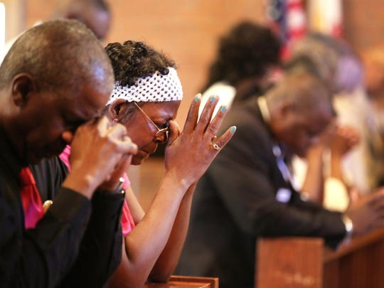 Worshippers pray during the Gaines United Methodist
