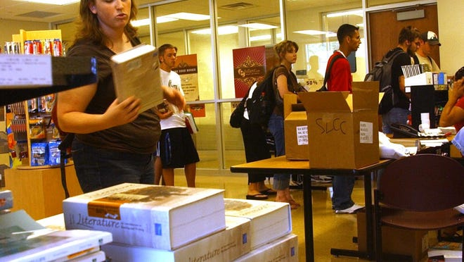 Mary Moody picks up her English textbook Monday moring in the bookstore at South Louisiana Community College.  By Leslie Westbrook August 21, 2006