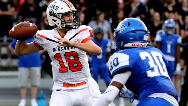 Blackman's quarterback Drew Beam (18) drops back to pass as Florence's (30) moves in for a tackle on Friday Aug. 24, 2018 at Braly Municipal Stadium, in Florence, Alabama.