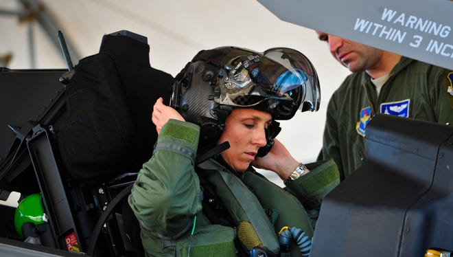 Lt. Col. Christine Mau, 33rd Operations Group deputy commander, puts on her helmet before taking her first flight in the F-35A on Eglin Air Force Base, Fla., May 5, 2015. Mau, who previously flew F-15E Strike Eagles, made history as the first female F-35 pilot in the program. (U.S. Air Force photo/Staff Sgt. Marleah Robertson)