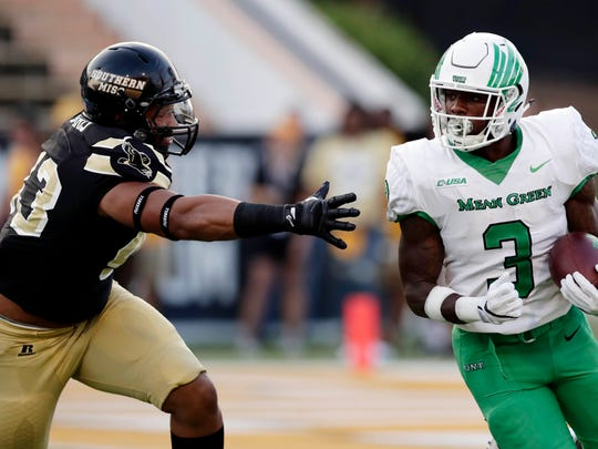 North Texas running back Jeffery Wilson (3) evades a tackle by Southern Mississippi defensive lineman LaDarius Harris (43) during their NCAA college football game in Hattiesburg, Miss., Saturday, Sept. 30, 2017. (AP Photo/Rogelio V. Solis)