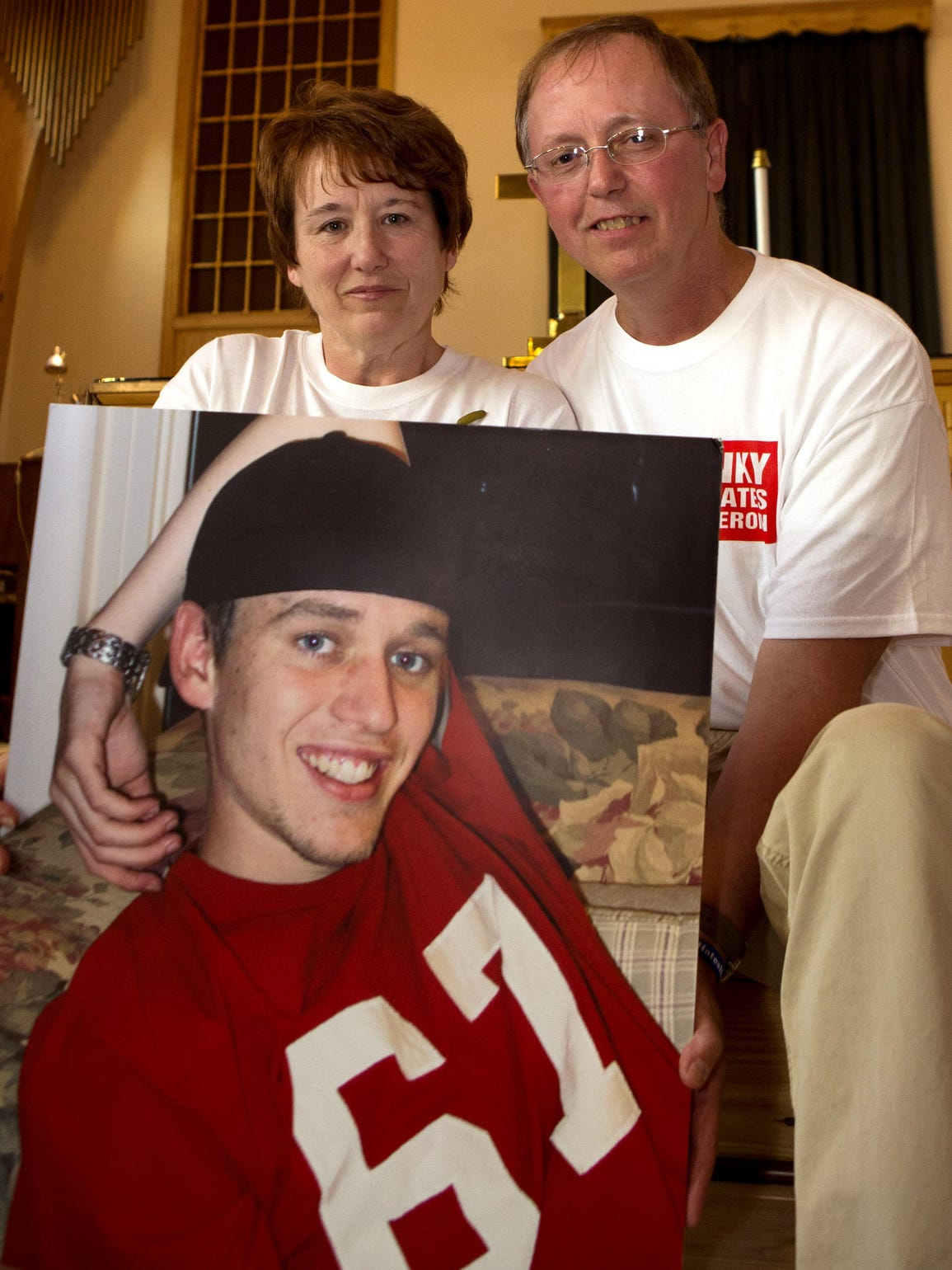 Holly and Eric Specht hold a picture of their son,