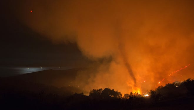 A fire tornado rises from advancing flames as the moon  is reflected in the ocean in the early morning hours of June 18 at the Sherpa Fire near Santa Barbara, California.