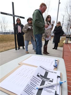 Members of the Mercy Junction Ministry prepare to lead a prayer circle for the uninsured in The Main Terrain city park Monday, Feb. 23, 2015, in Chattanooga, Tenn., before protesting against State Sen. Todd Gardenhire. Gardenhire, who was the featured speaker at Monday's Hamilton County Pachyderm Club's luncheon meeting, was one of seven Republican legislators to vote down Gov. Bill Haslam's Insure Tennessee plan earlier this month.