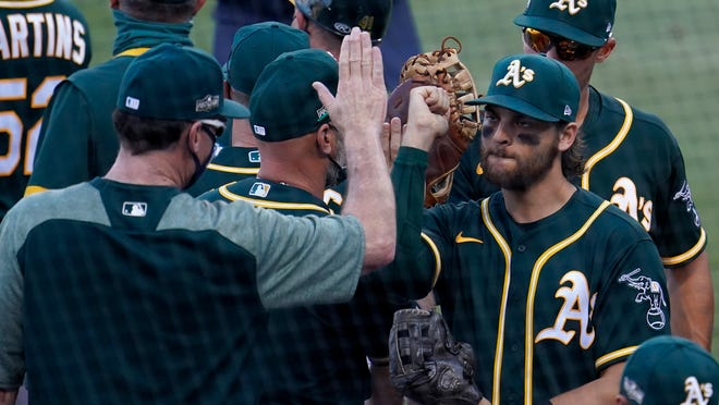 Oakland Athletics' Chad Pinder, right, celebrates with manager Bob Melvin after the Athletics defeated the Houston Astros in Game 3 of a baseball American League Division Series in Los Angeles, Wednesday, Oct. 7, 2020.