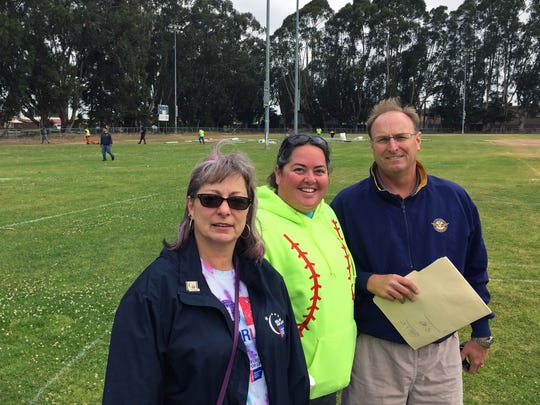 Peggy Borchard, Sara Papineau-Brandt, and Mark Kennedy set up for Relay for Life Salinas